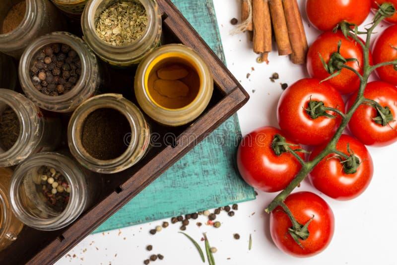 Especias y tarros de las hierbas Comida, ingredientes de la cocina, tomates de cereza, canela imagenes de archivo
