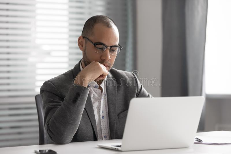 Espectacular hombre de negocios afroamericano usando laptop, proyecto de reflexión foto de archivo