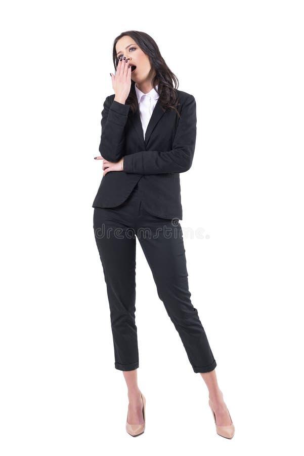 Espectador aburrido de la mujer de negocios en el seminario o la presentación que bosteza con la mano en boca imagenes de archivo
