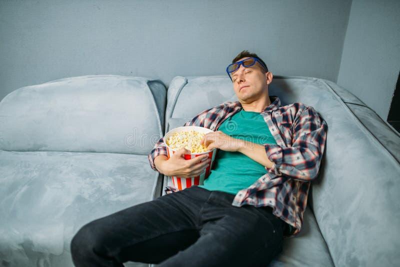 Espectador masculino que dorme no sofá no salão do cinema foto de stock