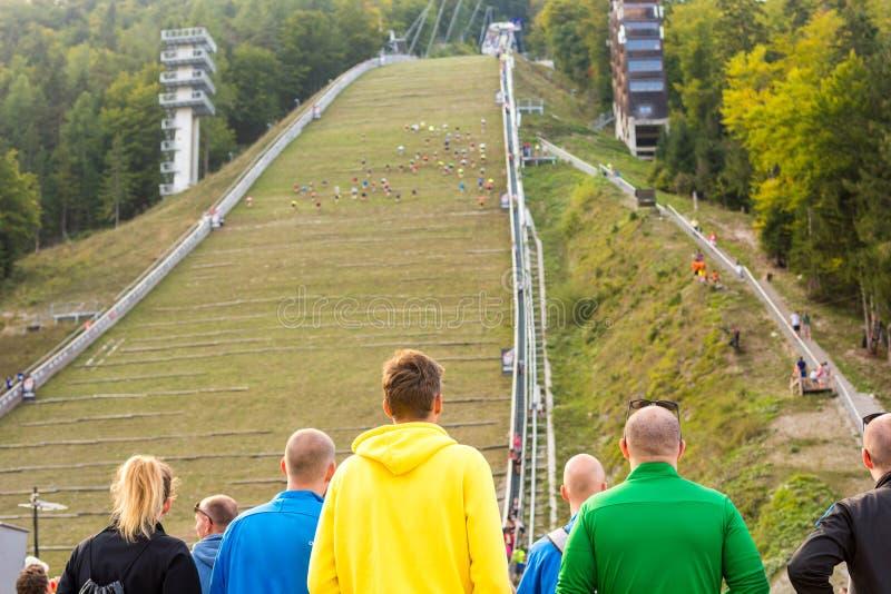 Espectadores en el acontecimiento deportivo que animan para los conmpetitors que corren hacia arriba en salto de esquí imagen de archivo libre de regalías