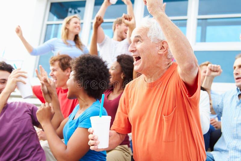 Espectadores que animan en el acontecimiento deportivo al aire libre imagenes de archivo