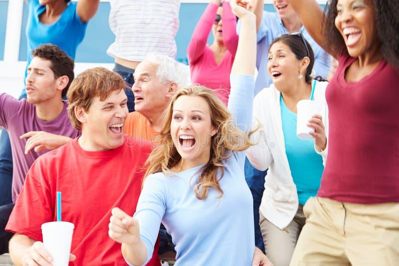 Espectadores que celebran en el acontecimiento deportivo al aire libre fotos de archivo libres de regalías