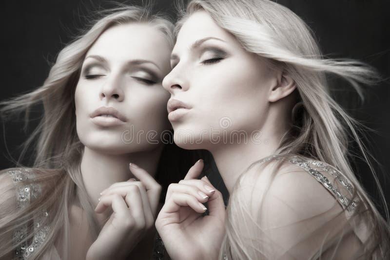 Espejo cercano atractivo hermoso de la mujer joven sobre gris fotos de archivo libres de regalías