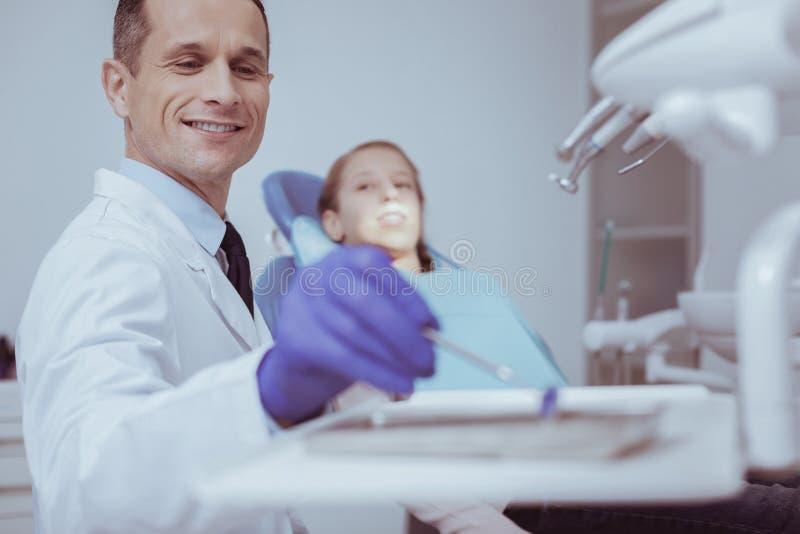 Espejo de boca masculino feliz de la cosecha del dentista imagenes de archivo