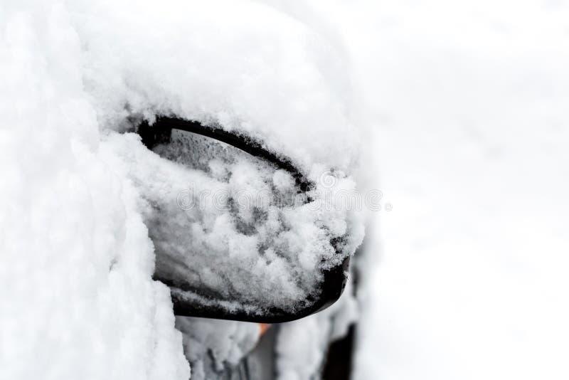 Espejo de coche cubierto con nieve después de nevada pesada en invierno fotografía de archivo