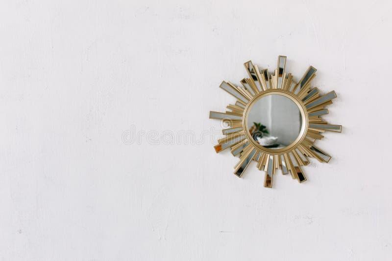 Espejo de la pared interior en la forma de un sol con los rayos de cobre amarillo del sol del metal como el marco aislado en la p fotografía de archivo libre de regalías