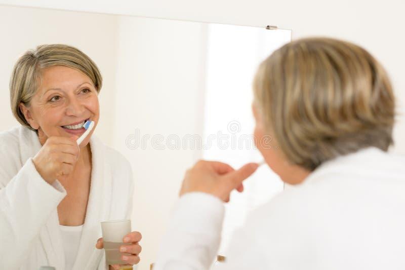Espejo del cuarto de baño de la mirada de los dientes de la mujer que aplica con brocha madura fotografía de archivo libre de regalías