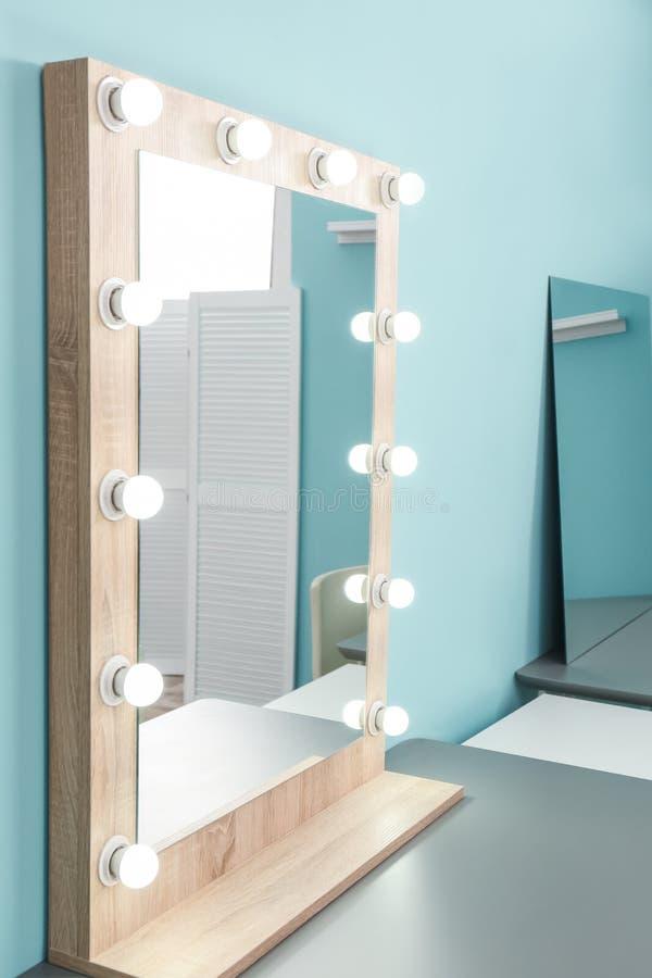 Espejo del maquillaje con las bombillas en la tabla en sitio foto de archivo