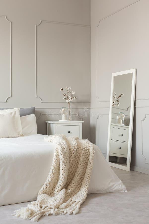 Espejo en marco en la pared gris del dormitorio escandinavo elegante interior con la cama gigante con la manta acogedora imagen de archivo