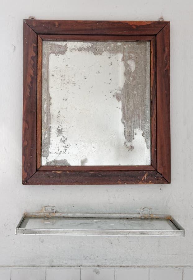 Espejo en un cuarto de baño dilapidado foto de archivo