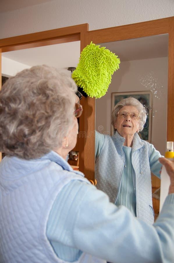 Espejo mayor de la limpieza de la mujer en casa imagen de archivo