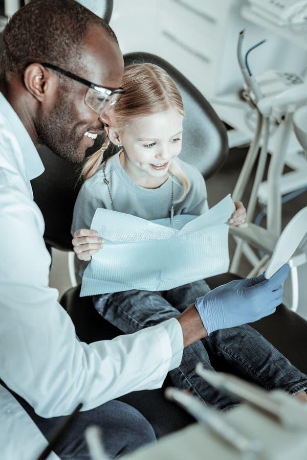 espejo positivo Abierto-sonriente de la tenencia del dentista contra niña fotos de archivo