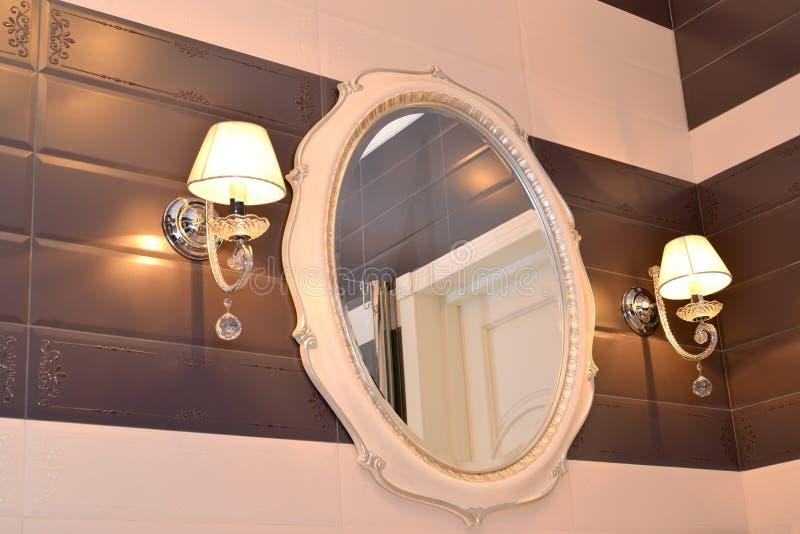Espejo y dos apliques en un cuarto de baño fotografía de archivo