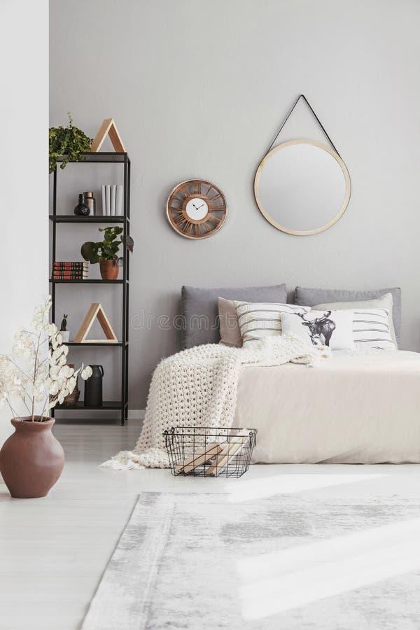 Espejo y reloj elegantes en la pared del dormitorio caliente del ethno con la cama gigante cómoda fotos de archivo