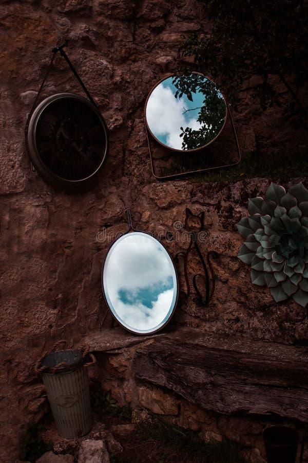Espejos que reflejan el cielo que se inclina contra una pared marrón al lado de un reloj fotografía de archivo libre de regalías