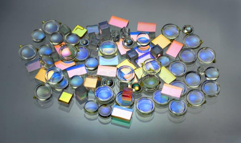 Espejos semitransparentes y prismas de las pequeñas lentes plásticas sobre el vidrio fotos de archivo libres de regalías