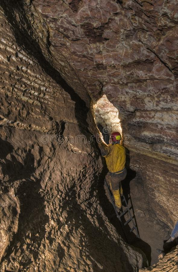 Espeleólogo na frente do lugar difícil na caverna imagens de stock royalty free