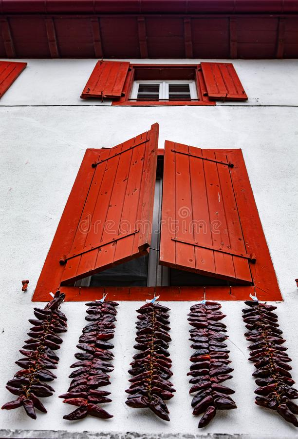 Red windows and Red hot chili peppers - Espelette. Espelette is known for its dried red peppers, used whole or ground to a hot powder, used in the production of royalty free stock images