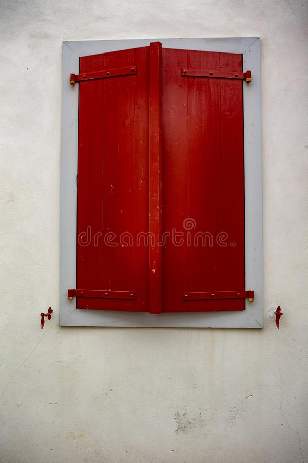 Red window - Espelette. Espelette is known for its dried red peppers, used whole or ground to a hot powder, used in the production of Bayonne ham. The peppers royalty free stock photo