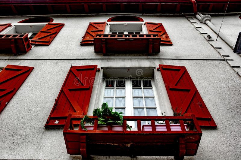 Red window - Espelette. Espelette is known for its dried red peppers, used whole or ground to a hot powder, used in the production of Bayonne ham. The peppers stock photos