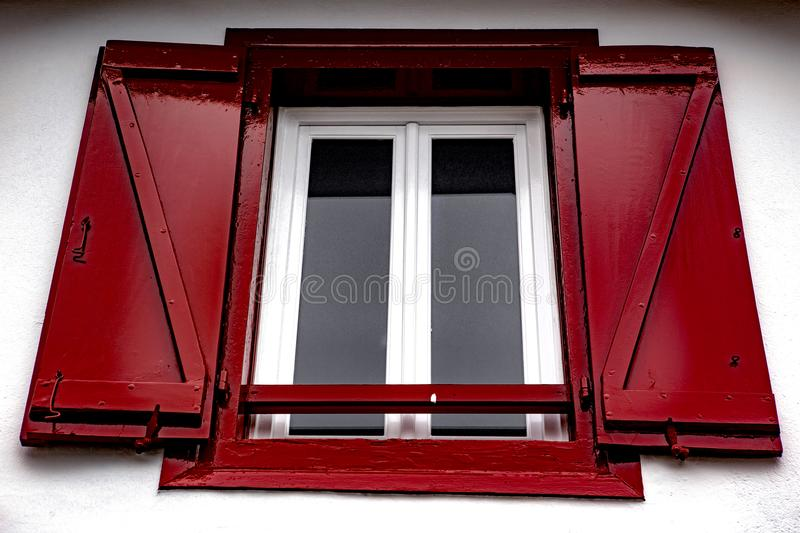 Red window - Espelette. Espelette is known for its dried red peppers, used whole or ground to a hot powder, used in the production of Bayonne ham. The peppers royalty free stock photos