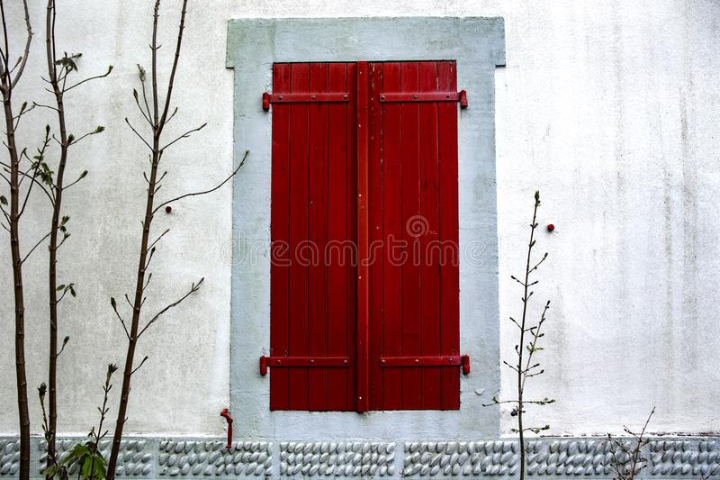 Red window - Espelette. Espelette is known for its dried red peppers, used whole or ground to a hot powder, used in the production of Bayonne ham. The peppers royalty free stock photography