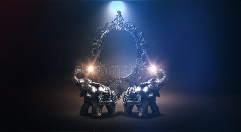 Espelhe dizer mágico, da fortuna e realização dos desejos Elefante dourado em uma tabela de madeira imagem de stock