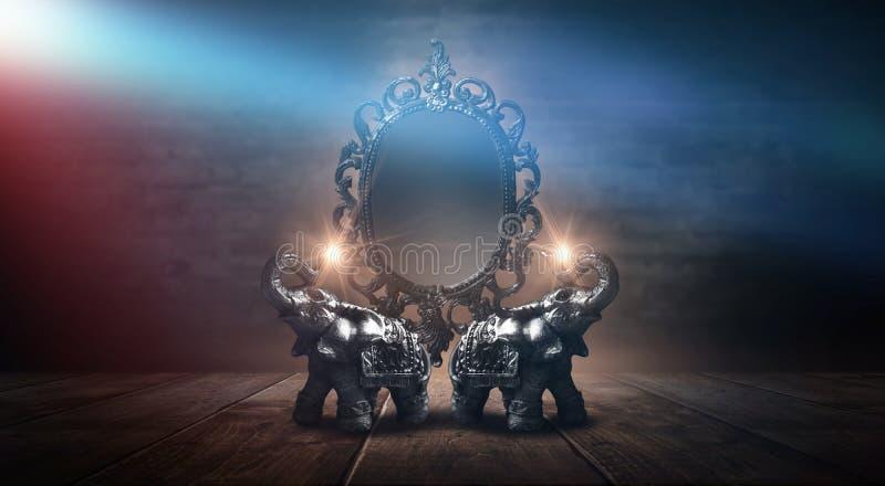 Espelhe dizer mágico, da fortuna e realização dos desejos Elefante dourado em uma tabela de madeira fotos de stock royalty free