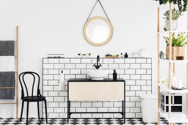 Espelho acima da bacia no interior branco do banheiro com plantas e cadeira preta ao lado da escada Foto real imagens de stock royalty free