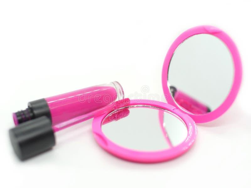 Espelho cor-de-rosa do bolso com os cosméticos brilhantes da mulher do batom em um fundo branco fotografia de stock