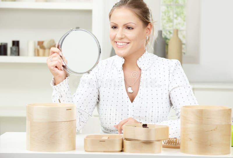 Espelho da terra arrendada da mulher nova fotografia de stock