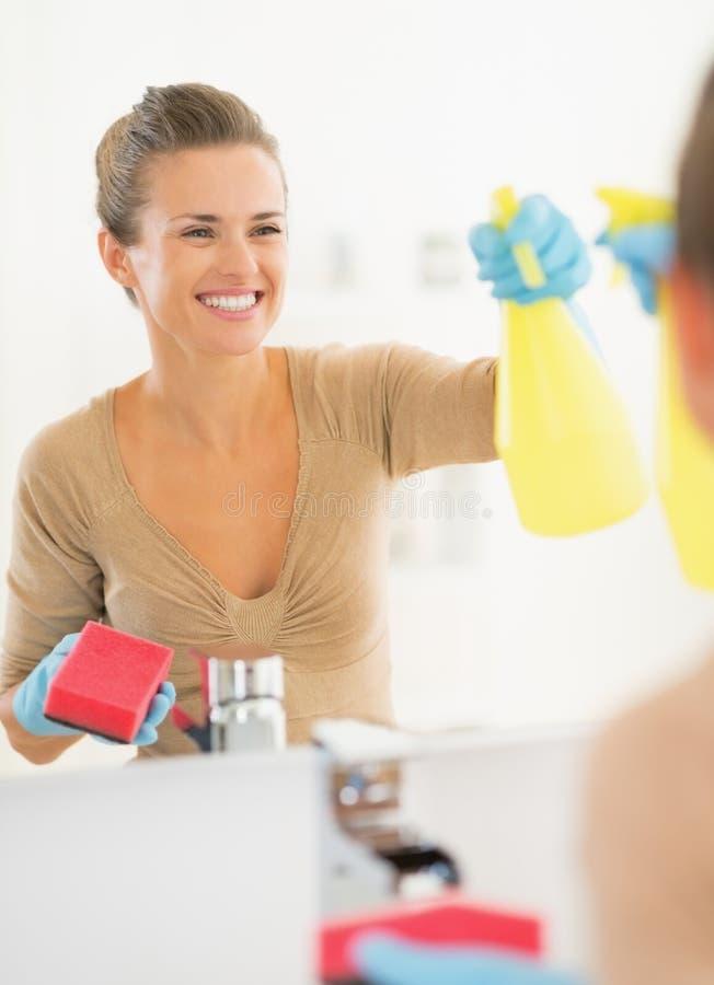 Espelho de sorriso da limpeza da dona de casa no banheiro fotografia de stock