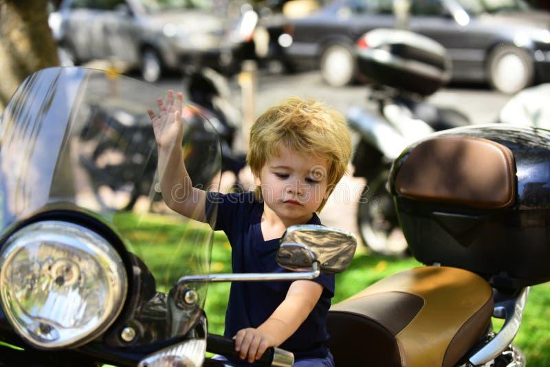 Espelho de vista distante Garoto bonitinho numa motocicleta olha no espelho, regras de trânsito, motorista competente, pequeno fotografia de stock
