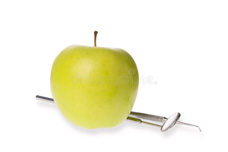 Espelho dental com ponta de prova do explorador perto da maçã verde isolada no branco Conceito dental oral da higiene foto de stock