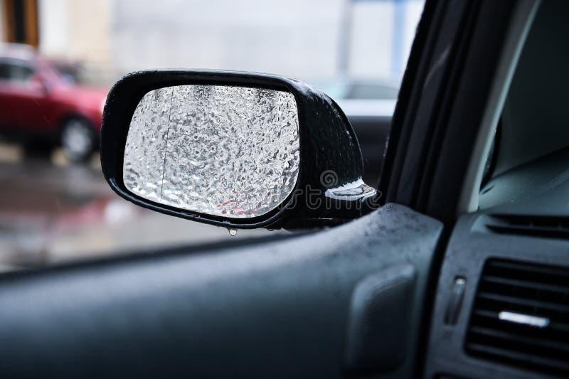 Espelho do veículo coberto no gelo durante a chuva de congelação foto de stock