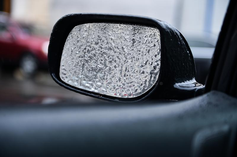 Espelho do veículo coberto no gelo durante a chuva de congelação imagem de stock royalty free