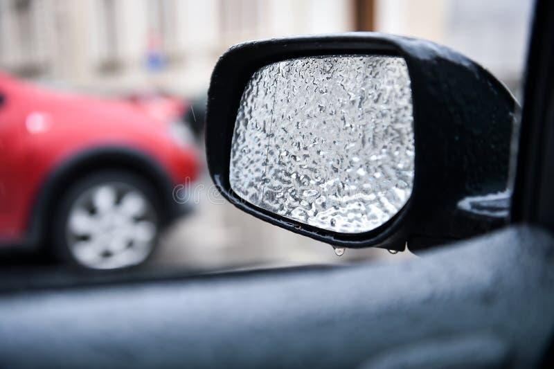 Espelho do veículo coberto no gelo durante a chuva de congelação imagens de stock