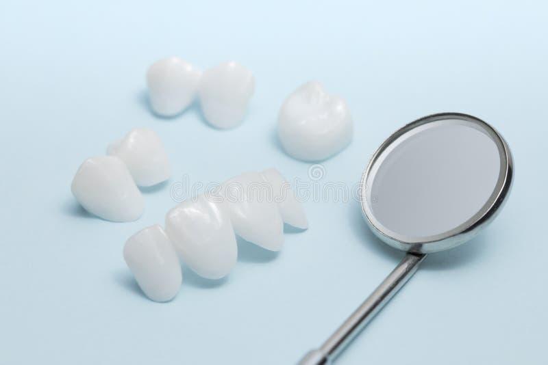 Espelho e dentaduras dentais em um fundo azul - folheados cerâmicos do zircão - lumineers imagens de stock royalty free