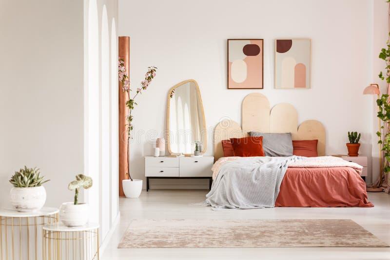 Espelho no armário branco ao lado da cama alaranjada sob cartazes no modo imagens de stock