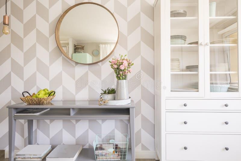Espelho no papel de parede modelado acima da tabela cinzenta com as flores em s fotografia de stock royalty free