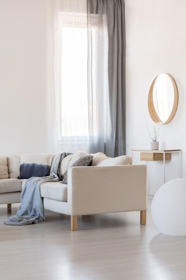 Espelho no quadro de madeira na parede branca da sala de visitas na moda interior no apartamento brilhante fotografia de stock