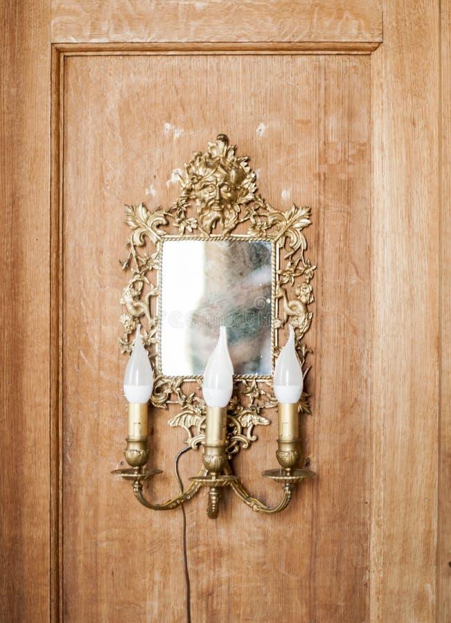 Espelho quadrado antigo com as lâmpadas na forma das velas em um quadro decorativo do ouro imagens de stock