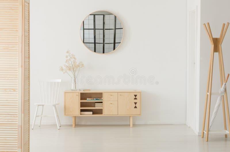 Espelho redondo acima do armário de madeira, foto real com espaço da cópia imagens de stock