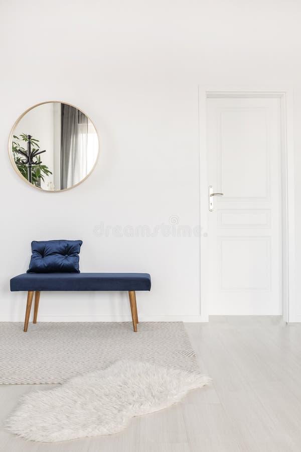 Espelho redondo elegante acima do banco de veludo no interior branco da sala de espera fotos de stock royalty free