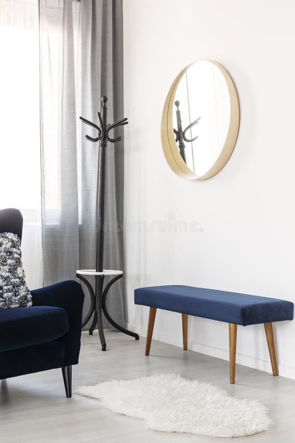 Espelho redondo elegante no quadro de madeira na parede branca da sala de visitas brilhante fotografia de stock