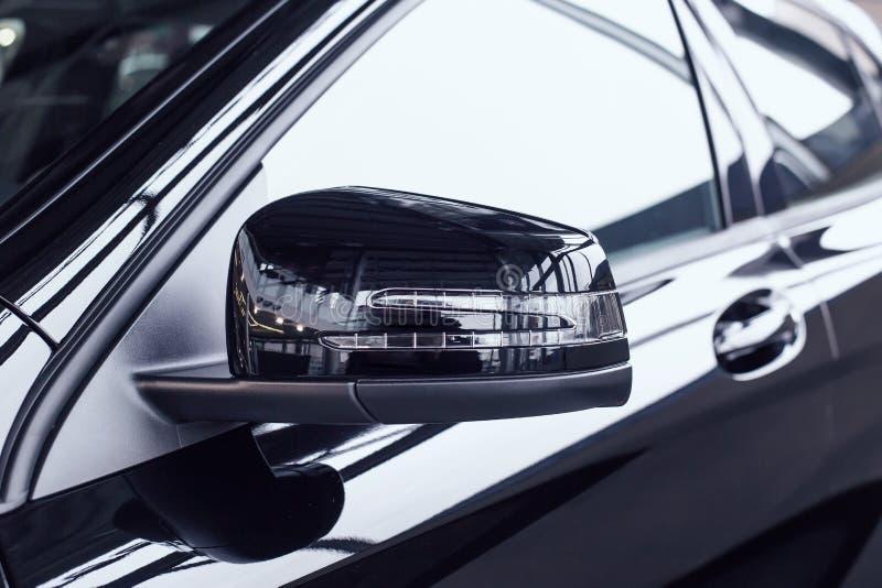 Espelho retrovisor lateral moderno num carro novo com um indicador de mudança de direção incorporado Carro negro numa concessioná fotografia de stock
