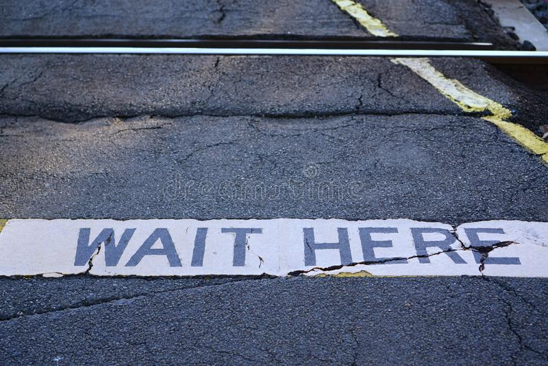 A espera aqui assina no cruzamento Railway imagem de stock royalty free