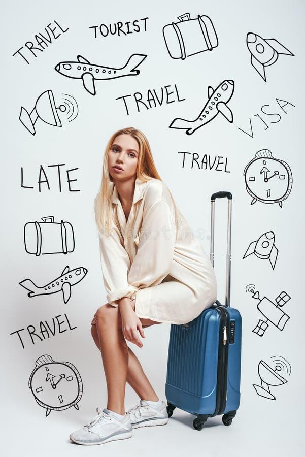espera Comprimento completo da mulher loura bonita que espera um voo e que senta-se em sua bagagem contra o fundo cinzento imagens de stock royalty free