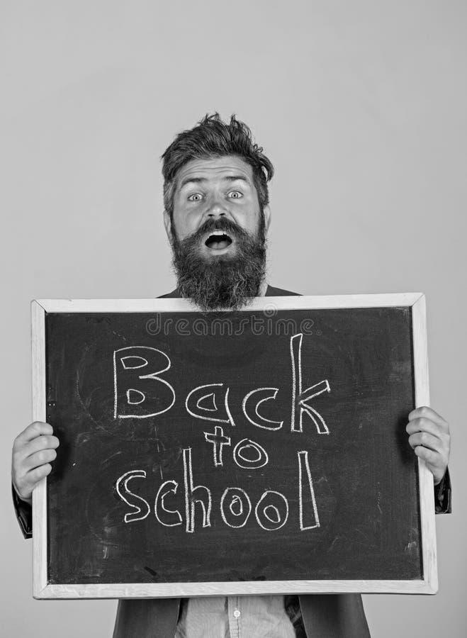 Espera da escola e do professor para voc? O professor ou o professor farpado est?o e guardam o quadro-negro com inscri??o de volt foto de stock